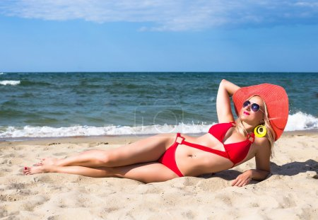 Young pretty woman in red hat relax near blue sea