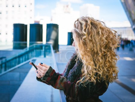 Young Hipster curly woman use her phone in the city downtown