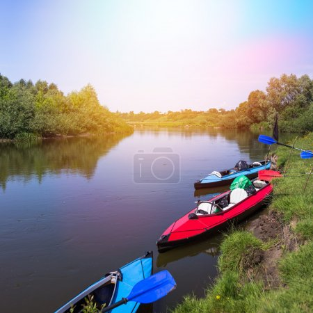 Red and blue kayaks on a river in beautiful nature