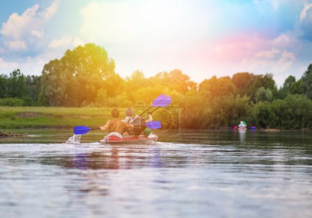 Young people are kayaking on a river in beautiful summer nature