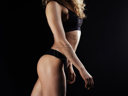 Picture of young female athlete back on dark background. Fitness model posing in studio
