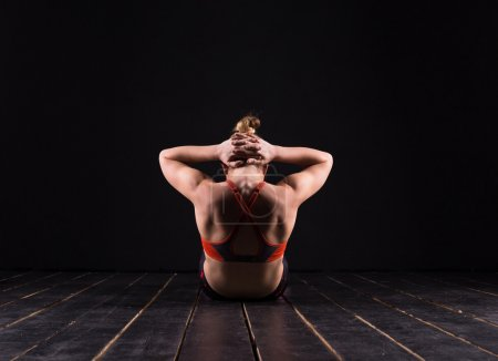 Beautiful young and fit fitness sport model doing yoga in dark studio