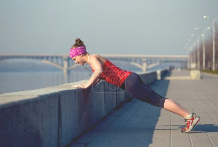 Sport woman doing push-ups outside on city quay in the morning