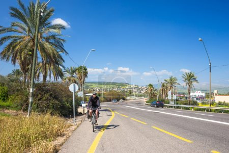 Happy biker on backdrop of palms in Israel
