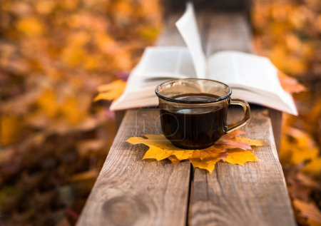 Photo for Hot coffee and red book with autumn leaves on wood background - seasonal relax concept - Royalty Free Image