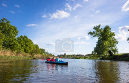 Young people are kayaking on a river in beautiful nature