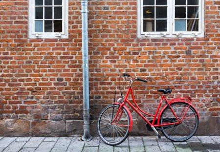 Red bicycle near red wall in Copenhagen, Denmark