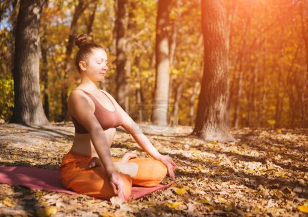Young woman doing yoga in morning autumn park