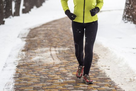 Young sport woman model jogging during winter training outside in winter