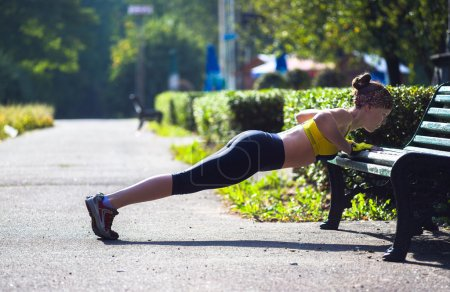 Sport woman doing push-ups during outdoor cross training workout