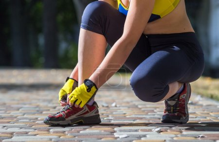 Sport woman tying running shoes during outdoor cross training workout