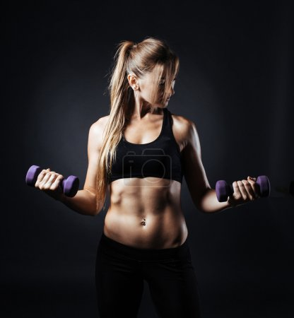 Muscular fitness woman with dumbbells on a dark background