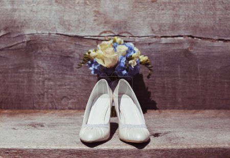 Wedding bouquet and shoes in sunny wedding day