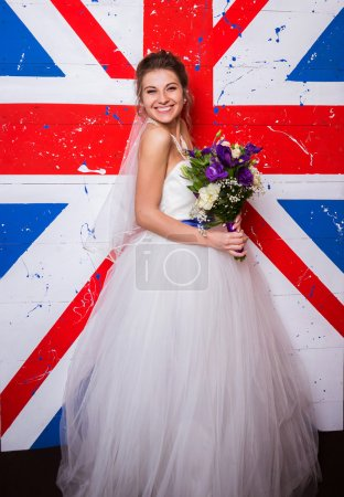Young beautiful bride posing on english flag background