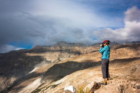 tourist with camera and mountains