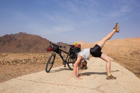 Young woman relaxing yoga during bicycling trip
