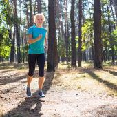 """Постер, картина, фотообои """"Бегун женщина, тренинг по лесной дороге в красивой природой."""""""