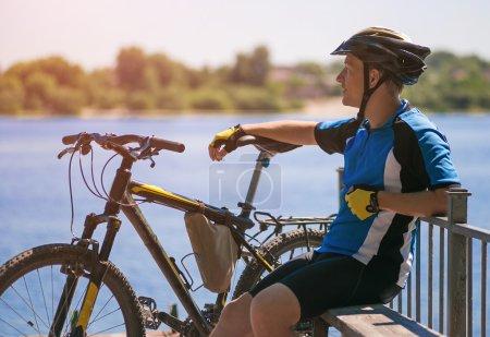 Photo pour Jeune cycliste se détendre dans la jetée près de la rivière dans la journée ensoleillée d'été - image libre de droit