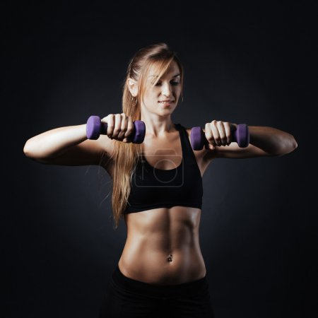 Muscular fitness woman with dumbbells