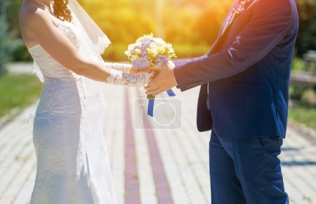 Wedding couple holding hands in sunny day. Happy young bride and groom