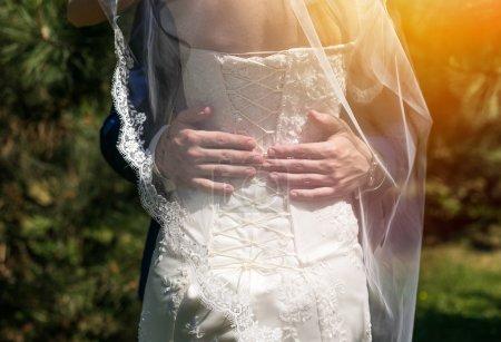 Photo pour Couple de mariage tenant la main dans la journée ensoleillée. Mariée heureuse et marié - image libre de droit