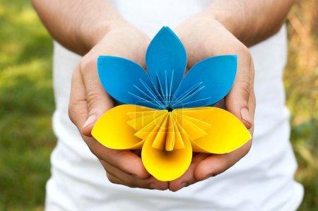 Photo pour Mains tenant un origami de fleur de papier jaune bleu - image libre de droit