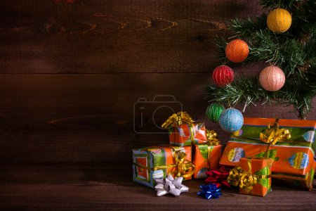Many Christmas presents under the tree on plank background