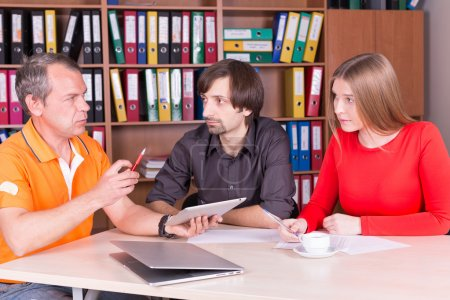two men and one woman have meeting in office