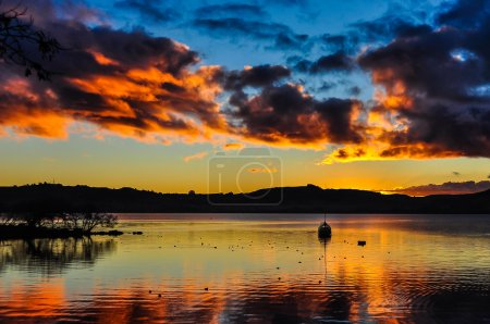 Colorful sunset with a boat  in Lake Taupo, New Zealand