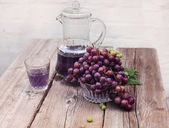 Fresh green and blue grapes.A carafe of grape juice