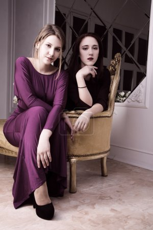 two beautiful sexy elegant girl in  evening dresses seating in a