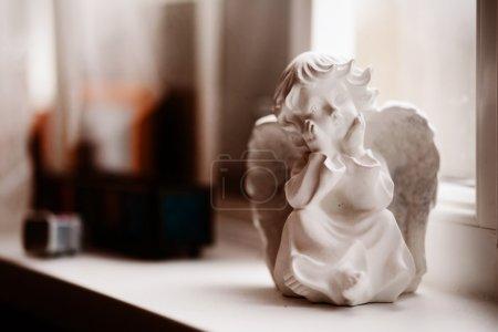 Cherub statuette on a windowsill