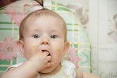 Malé dítě dívka sedí na vysoké židličce a snědl