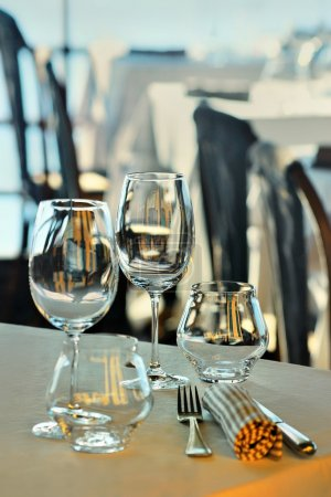 Wine glasses and dishes on the summer terrace of the restaurant