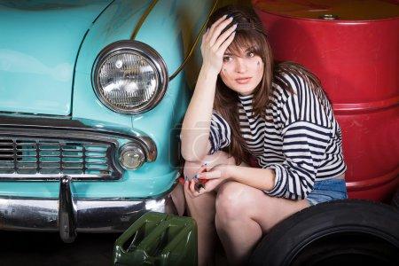 Photo pour Jeune femme attrayante dans une casquette de baseball se trouve fatigué dans le garage près de la voiture rétro avec des outils. Fille tenant pinces et a pris la tête . - image libre de droit