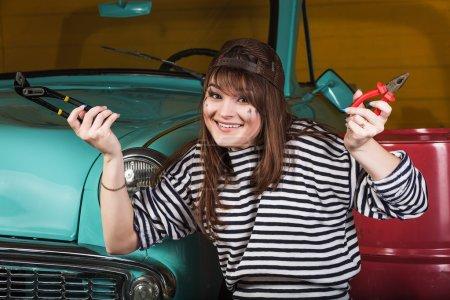 Photo pour Attrayant jeune femme gaie dans une casquette de baseball se trouve dans le garage près de la voiture rétro avec des outils. Fille tenant des pinces et une clé réglable et souriant - image libre de droit
