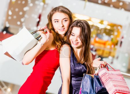 sale, tourism, shopping and happy people concept - two beautiful women with shopping bags in the shopping center