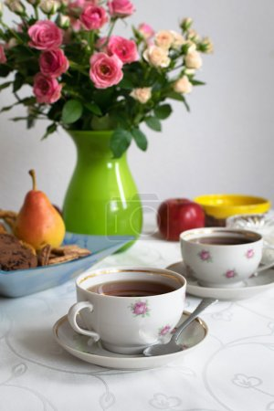 The tea time. Two cups of black tea on the white tablecloth with bowl of sugar, fruits, cookies and vase with roses. Selective focus. Vintage background.