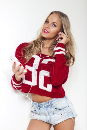 Photo for Beautiful stylish blonde woman with long curly hair wearing red shirt,jeans shorts poses listening music, holding phone and earphones in ears on white studio isolated background.Pink lips.Perfect - Royalty Free Image