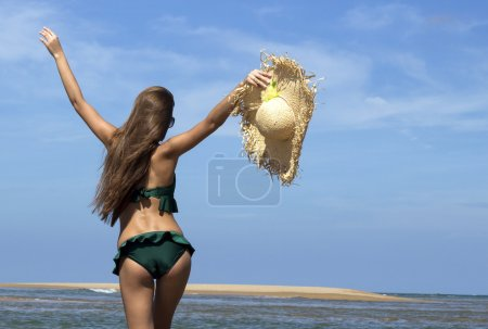 Hot beautiful woman in sunhat, sunglasses and bikini standing with her arms raised up enjoying looking view of beach ocean on hot summer day. Vacation.Photo from Phuket island. Thailand