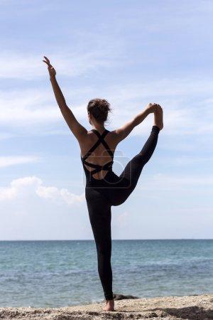 Photo pour Yoga femme pose sur la plage près de la mer et des rochers. Phuket, Thaïlande - image libre de droit