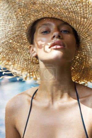 Woman in hat and black stylish swimsuit poses near swimming pool enjoying sun. Phuket island, Thailand. High fashion look.