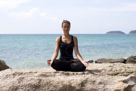 Photo for Yoga woman poses on beach near sea and rocks. Phuket, Thailand - Royalty Free Image