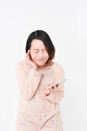 Japanese woman listens music on headphones