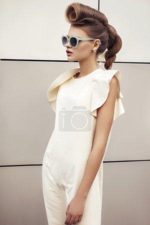 schöne Mädchen in weißem Kleid mit lockigem Haar auf hitech Hintergrund