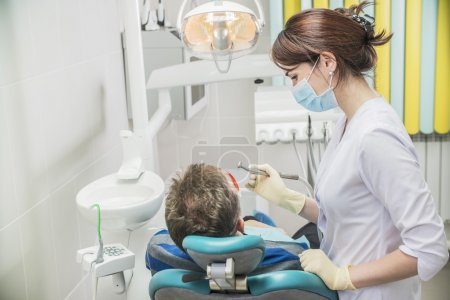 dental care concept stomatology inspection. the patient lies in a chair in dentistry in front of him a hand with drill