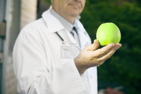 closeup of green Apple in the hand doctor nutritionist