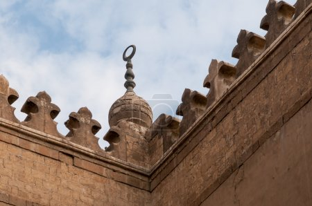 An Islamic crescent on top of a mosque with cloudy...