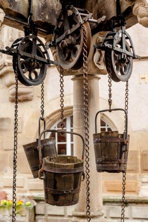 Photo pour Puits d'eau traditionnel avec seaux fixes dans un village d'Alsace, France - image libre de droit