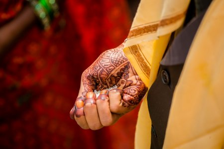A Hindu bride holds an handful of rice during  a b...